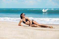 Slanke en gelooide meisje van de close-up het mooie luxe in een zwarte bikini op het strand de oceaan Sexy gelooid lichaam, vlakk Stock Fotografie