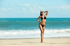 Slanke en gelooide meisje van de close-up het mooie luxe in een zwarte bikini op het strand de oceaan Sexy gelooid lichaam, vlakk Stock Afbeelding