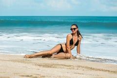 Slanke en gelooide meisje van de close-up het mooie luxe in een zwarte bikini op het strand de oceaan Sexy gelooid lichaam, vlakk Royalty-vrije Stock Foto's