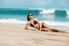 Slanke en gelooide meisje van de close-up het mooie luxe in een zwarte bikini op het strand de oceaan Sexy gelooid lichaam, vlakk Stock Afbeeldingen