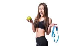 Slanke en gezonde jonge die de maatregelenband en appel van de vrouwenholding op witte achtergrond wordt geïsoleerd Gewichtsverli Royalty-vrije Stock Foto