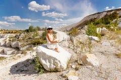 Slanke gelooide vrouwenzitting op een stuk van marmer, de bergen, de hemel, de stoffige weg Royalty-vrije Stock Foto