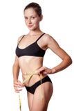 Slanke geschikte gelukkige jonge vrouw met maatregelenband die haar taille met zwart die ondergoed meten, op witte achtergrond wo Royalty-vrije Stock Foto