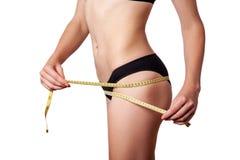 Slanke geschikte gelukkige jonge vrouw met maatregelenband die haar taille met zwart die ondergoed meten, op witte achtergrond wo Royalty-vrije Stock Afbeelding