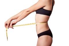Slanke geschikte gelukkige jonge vrouw met maatregelenband die haar taille met zwart die ondergoed meten, op witte achtergrond wo Stock Afbeeldingen