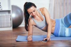 Slanke geschiktheids jonge vrouw die oefening thuis met smartphone doen Stock Afbeelding