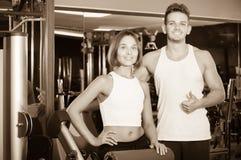 Slanke jonge man en vrouw die pauze nemen tussen het uitoefenen in gymnastiek stock afbeeldingen