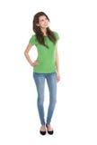 Slanke jonge vrouw die groene overhemd en jeans in volledig lichaam dragen Stock Foto's