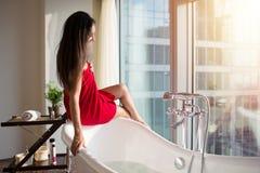 Slanke jonge vrouw in handdoekzitting op badkuip in luxueuze badkamers stock fotografie