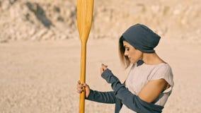 Slanke jonge vrouw met een peddel tegen de bergen Fantastische droom stock videobeelden