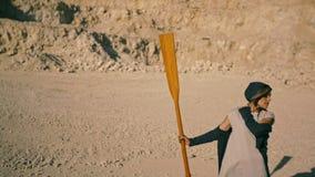Slanke jonge vrouw met een peddel tegen de bergen Surrealistische scène stock videobeelden