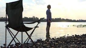 Slanke Mensentribunes blootvoets in Water op een Riverbank en Levensonderhoud een Steen in slo-Mo stock videobeelden