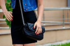 Slanke modieuze vrouw in een kleine zwarte kleding met gewatteerd stock foto's