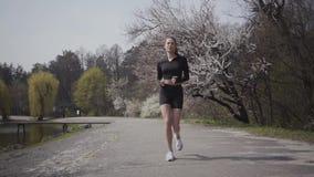 Slanke sporten jonge vrouw in sportkleding die op riverbank lopen Actieve levensstijl, sport De dame die haar lichaam binnen houd stock videobeelden