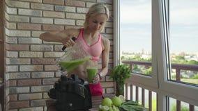 Slanke sportieve vrouw die een eigengemaakte groene detox maken smoothie stock footage