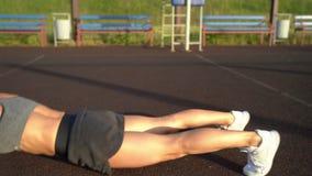 Slanke vrouw die duw op oefening doen bij sportengrond stock video