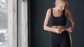 Slanke vrouw die taille met meetlint in centimeters meten stock footage