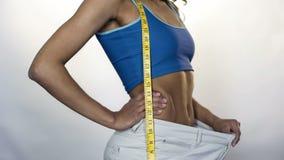 Slanke vrouw die taille die van grote broeken trekken weg, gewichtsverlies, training tonen stock afbeeldingen