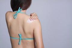 Slanke vrouw die zonbescherming op haar lichaam toepassen sunb stock afbeeldingen