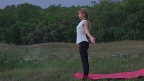 Slanke Vrouw het Praktizeren Yoga Asanas op de Open plek in het Stadspark stock footage