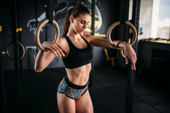 Slanke vrouwelijke atletenoefening op gymnastiek- ringen Stock Foto