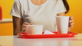 Slanke vrouwelijke student die snel voedseldienblad in cafetaria dragen, die bij lijst zitten stock videobeelden
