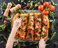 Slanke vrouwenhanden die de grote eigengemaakte rand van de paddestoelpizza snijden Stock Afbeeldingen