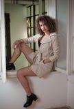 Slankt ungt bärande vitt lag för modemodell i fönsterram Älskvärd sexig trendig kvinna med ljus - brunt lockigt hår Royaltyfri Foto