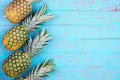 Slanted pineapples arranged on wooden table Stock Images