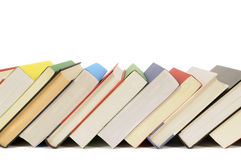 Slanted row of books, leaning, isolated on white background, copy space. Slanted row of colorful books isolated on a white background Royalty Free Stock Photos