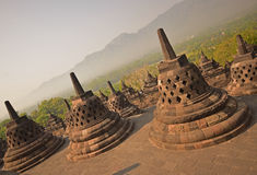 Slanted View of Borobudur Giant Stupas during late sunrise with misty feeling among the forest in the background Stock Images