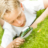 Slanted view of boy in white with magnifying glass Stock Image