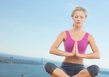 Slanted woman meditating against coastline royalty free stock image