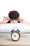 Slaperig Aziatisch meisje met oogmasker en wekker stock fotografie