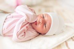 Slaperig babyclose-up in een babywieg stock afbeelding