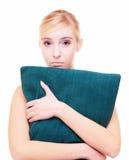 Slaperig blond meisje met groen die hoofdkussen over wit wordt geïsoleerd stock foto's