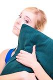 Slaperig blond meisje met groen die hoofdkussen over wit wordt geïsoleerd royalty-vrije stock foto