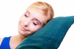 Slaperig blond meisje met groen die hoofdkussen over wit wordt geïsoleerd stock fotografie