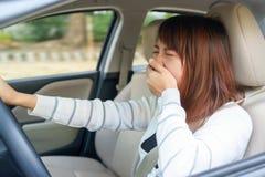 Slaperig, geeuw die, dichte ogen jonge vrouw haar auto na lang drijven stock foto's