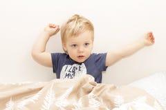 Slaperig kind in de bed ontwaken of het krijgen van slaap stock afbeelding