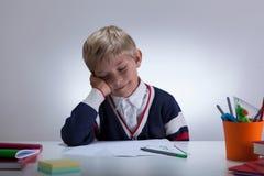 Slaperig weinig jongen naast bureau stock afbeelding
