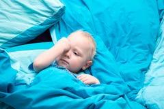 Slaperige baby in de voederbak met blauw beddegoed stock foto's