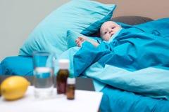 Slaperige baby in de voederbak met blauw beddegoed stock foto