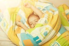 Slaperige baby in kleurrijke deken stock fotografie