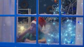 Slaperige dromende jongen die in venster in Kerstmistijd kijken stock video