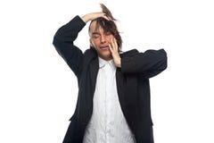 Slaperige jonge mens wat betreft zijn hoofd Stock Fotografie