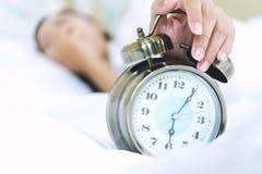 Slaperige jonge vrouw in bed met gesloten ogen het uitbreiden van hand tot ala stock foto