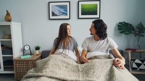 Slaperige meisje en kerelontwaken in bed die thuis omhoog en slaapkamer worden verlaten stock videobeelden