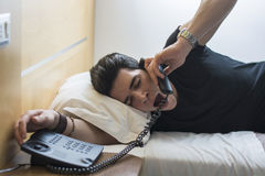 Slaperige Mens die op Bed terwijl het Spreken bij geeuwen Stock Fotografie