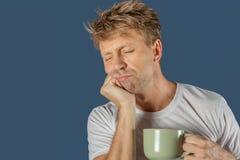 Slaperige mens met een mok van hete drank Vroege ochtend royalty-vrije stock afbeelding